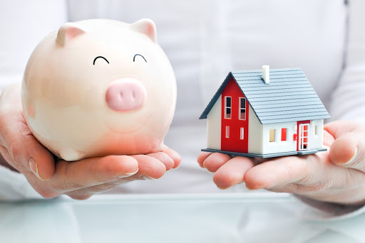 depiction of mortgages for landlords using piggy bank and a model home